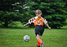 Go, Girl!. Little girl running after a soccer ball royalty free stock images