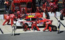 Go, Go, Go!!!. Elliot Sadler's pit crew races to complete their pit stop as fast as possible as NASCAR officials watch closely during 2007 spring race at Royalty Free Stock Photography