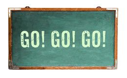"""`Go! Go! Go!"""" motivational text word message written on a wide green old grungy vintage wooden chalkboard royalty free stock photography"""