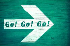 """`Go! Go! Go!"""" motivational text written on a white directional arrow pointing towards right painted on a green wood Royalty Free Stock Image"""