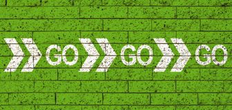 Go Go Go white word text and direction arrows on green stone brick wall background as motivational message stock illustration