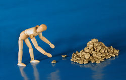 Go For The Gold. Mannequin reaching for gold nuggets.  Metaphor Stock Images