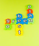 Go green best plan. Text ' go green best plan ' created using jigsaw style colored pieces on pale green background Royalty Free Stock Images