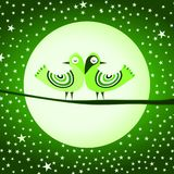 Go Green Birds Ethnic Feathers. A pair of birds with ethnic feathers on a tree branch and green background with full moon and stars. Go green save the planet Stock Photo