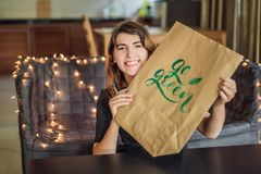 Go green. Calligrapher Young Woman writes phrase on white paper. Inscribing ornamental decorated letters. Calligraphy royalty free stock photography