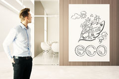 Go green concept. Handsome businessman in modern office looking at eco sketch on wooden wall. Go green concept. 3D Rendering Stock Images