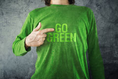 Go green. Man pointing to title printed on his shirt Royalty Free Stock Photography