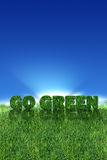 Go Green sign over fresh grass. Textured go green sign over fresh grass. Clear blue sky background Royalty Free Stock Images