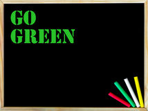 Go Green text on blackboard Stock Images