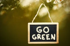 Go green written on black chalk board hanging from a tree. Stock Image