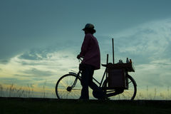Go Home. Silhouette of a person who was walking home while pushing his bicycle Royalty Free Stock Image