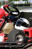 Go Kart Closeup. Go Kart in the pit stop closeup with a helmet in the seat and race track in the background Stock Photos