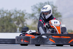 Go-kart pilot racing. Young man go-kart pilot is racing a race in an outdoor go karting circuit - focus on the helmet Royalty Free Stock Images