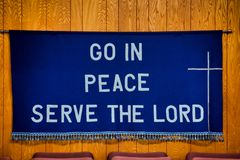 `Go in Peace Serve the Lord` written on Dark Blue Cloth hanging on the wall behind red chairs stock image