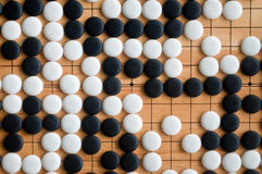 Go pieces on wooden board Royalty Free Stock Image