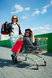 Go shopping with best friend. Female friends having fun with with trolley cart outdoors Stock Photography