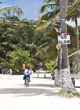 Go slow Belize. CAYE CAULKER, BELIZE - SEPTEMBER 20, 2013: Girl going to school by bike besides the national Belizean advise go slow sign. September 20, 2013 in Stock Photos