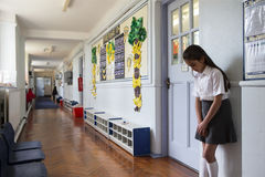 Go Stand in the Corridor. Naughty school girl stands in the corridor after being sent out of class Royalty Free Stock Photography