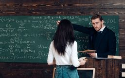 Go to chalkboard. Teacher call girl student to chalkboard. Genius man and woman rear view in classroom. Education in stock photo