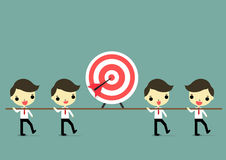Go to goal with teamwork. Four businessman carry wood which has target and arrow above it Royalty Free Stock Photo
