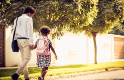 Go to school. African American father and his daughter walking trough park. From back stock photo