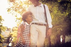 Go to school and work. African American father and his daughter walking trough park stock photography