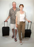 On the go tourists. Mature couple wheeling suitcases as if on vacation royalty free stock photos