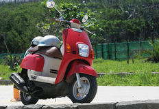 Go Travel with a Red Scooter. A red scooter has been parked by the side of the road. It has been used for travel in the countryside stock images