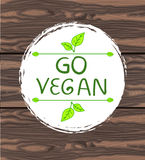 Go vegan handwritten text in circle hand drawn frame with vegnette and hand drawn leaves on brown background. Stock Photo