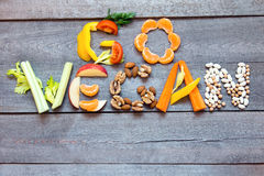 Go Vegan. Words `Go Vegan` written with vegetables, fruits, nuts and legumes on rustic wooden background, concept - organic ingredients for healthy vegan food stock photo