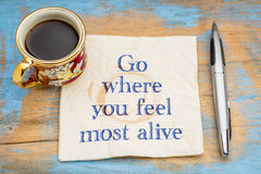 Go where you feel most alive. Inspirational handwriting on a napkin with a cup of coffee Royalty Free Stock Photos