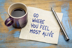 Go where you feel most alive. Inspirational handwriting on a napkin with a cup of espresso coffee royalty free stock images