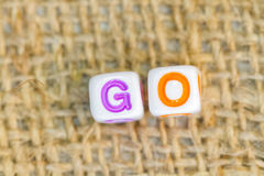 GO word cube beads on sockcloth Royalty Free Stock Photo