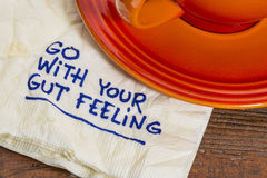 Go with your gut feeling. Advice or motivational reminder on a napkin with cup of coffee stock image