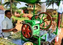 Goa, Índia - 16 de novembro de 2014: Homem novo que cozinha e que vende o suco popular do junco da rua do ` s da Índia fotografia de stock