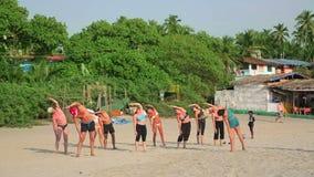 GOA, ÍNDIA - EM MARÇO DE 2013: Ioga praticando dos povos na praia vídeos de arquivo