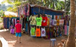 Goa, Индия - 16-ое декабря 2016: Местный житель продавая одежды и аксессуары на пути к Anjuna приставают к берегу Стоковые Изображения RF