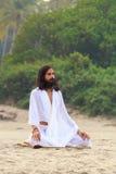 GOA, INDE - AVR. 24, 2014 : L'homme s'est habillé dans le yoga de pratiques en matière de blanc dans Arambol, Goa, Inde en avril  Image stock