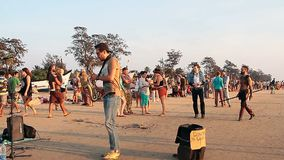 Unidentified people relaxing on the beach to the sound of a saxophone. Goa, India – February 12, 2016: Unidentified people relaxing on the beach to the sound stock video footage