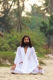 GOA INDIA, APR, - 24, 2014: Mężczyzna ubierał w biel praktyk joga w Arambol, Goa, India na APR 24, 2014 Zdjęcia Stock
