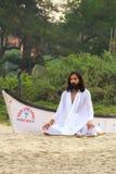 GOA, INDIA - APR. 24, 2014: Man dressed in white practices yoga in Arambol, Goa, India on APR. 24, 2014. Royalty Free Stock Photo
