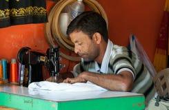 Goa, India - Januari 2008 - Lokale kleermaker die sommige snelle wijzigingen maken bij zijn uiterst kleine winkel stock afbeelding