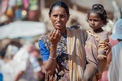 Goa, India - Januari 2008 - Vrouwelijke bedelaar met een kind bij een beroemde wekelijkse vlooienmarkt in Anjuna Stock Foto's