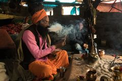 Hermit sadhu smokes a narcotic compound sitting in a hut emitting a large tangle of smoke. Babba ascetic lives in poor conditions. Goa, INDIA - January 11, 2018 stock image