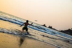 Goa, India - Maart 23, 2017: Actieve mens het spelen frisbee op het strand van de arambolzonsondergang Royalty-vrije Stock Foto's