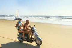Brutal man and woman rides on a des. Goa, India - March 03, 2015: Brutal man and woman rides on a deserted beach along the ocean at motorcycle stock photos