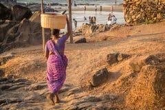 GOA INDIA, MARZEC, - 4: Kobieta w sari z koszem na jej głowie wal zdjęcie royalty free