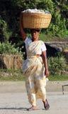 GOA, INDIEN - indische Frau mit großem Korb auf ihrem Kopf Stockbild