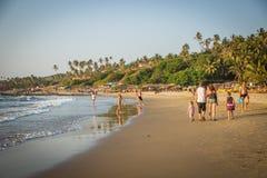 GOA, INDIEN - 4. MÄRZ: Familie gehen an wenigem Vagator-Strand stockbild
