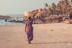 GOA, INDIEN - 4. MÄRZ: Frau in den Sari mit Korb auf ihrem Kopf wal Stockfotos